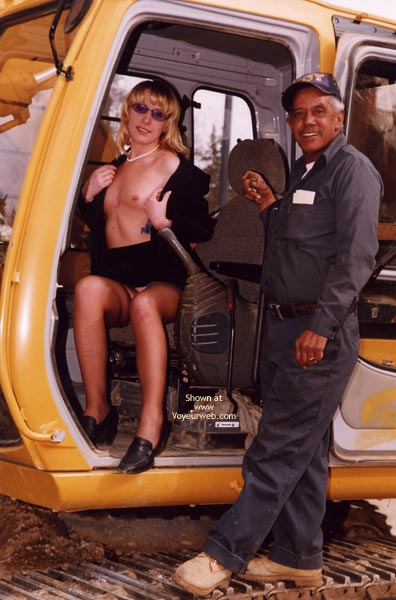 Topless Equipment Operator , Topless Equipment Operator, Blonde With Sunglasses Pearl Necklace, Blonde Sitting In Tractor With Top Open, Tractor Operator Next To Topless Blonde
