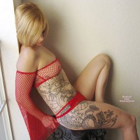 Full Body Tatoo - Blonde Hair, Pierced Nipples, Small Breasts , Red Net Top, Pierced Nipple With Ring, Unfinished Tatoo, Posing On Furniture, Looking Down, Red Fishnet Strapless Top With Long Sleeves, Full Body Tatoo Needs Filling Color, Red Two Strap Panties, Posing By Window, Nipple Ring