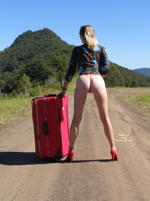 BOOTY ON THE ROAD - Blonde Hair, Heels, Long Legs , Tall Blonde, Red High Heels, Bond Girl Poster Pose, Black Blue Flower Blouse, Tall Slender, Slender Legs, Rear View Of Legs And Bum, Curvy Legs