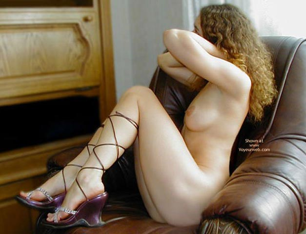 Naked In The Living Room , Naked In The Living Room, Nipple Shot, Naked On The Chair With Purple Heels, Posing In Leather Chair, Curly Auburn Hair, Strappy Purple Platform Heels, Legs Pulled Up, Arms Forward, Running Fingers Through Her Hair