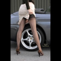 Girl Standing In Front Of A Porsche - Long Legs, Rear View, Stockings , Girl Standing In Front Of A Porsche, Showing Her Long Legs, Lifting Her Skirt, Black Stockings, Brown High Heels, Rear Shot, White Skirt, Leg And Tire, Back Seam Stockings, Standing Beside A Car