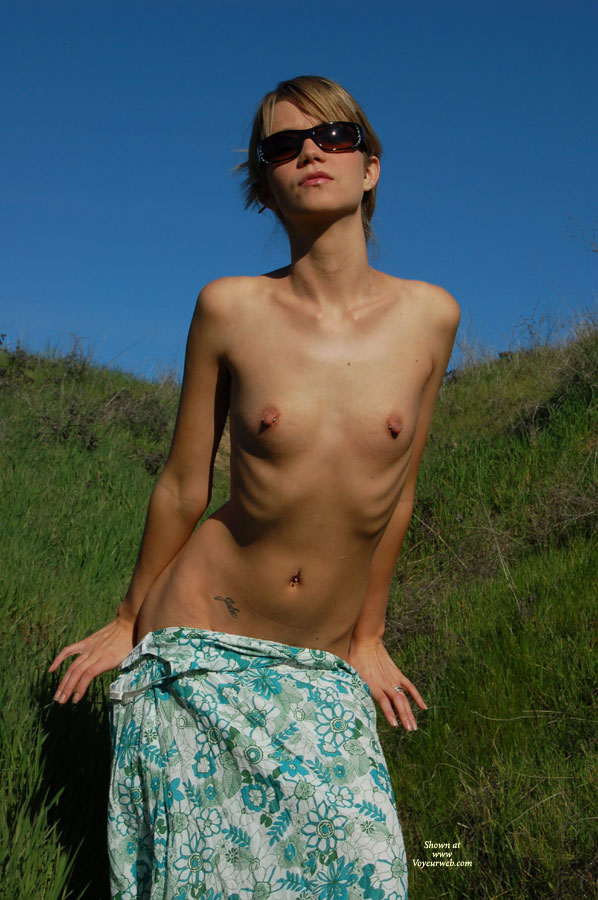 Blonde With Pierced Nipples Undressing Outside. - Blonde Hair, Pierced Nipples, Small Breasts, Sunglasses , Pushing Dress Down, Small Pierced Breasts On A Beautiful Woman., Tight Body Showing Rib Cage And Belly Button Jewelry, Flat Chested Female, Slim Body, Skinny Female Sliding Off, Visible Ribcage, Blond Girl With Sunglasses With Flower Print Dress Below Her Waist, Short Hair, Standing On Beach
