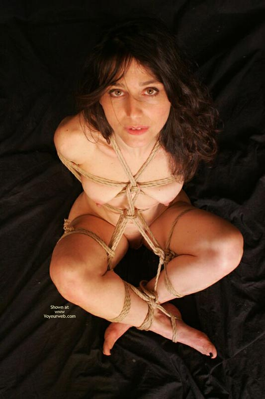 Arms Behind In Rope Bondage - Black Hair, Bondage, Nude Amateur , All Tied Up!, Sitting With Legs Crossed Above Ankles, Green Eyes, Sitting Nude Bound, Looking Up At Viewer, All Knoted Together, Tied Up For Transport
