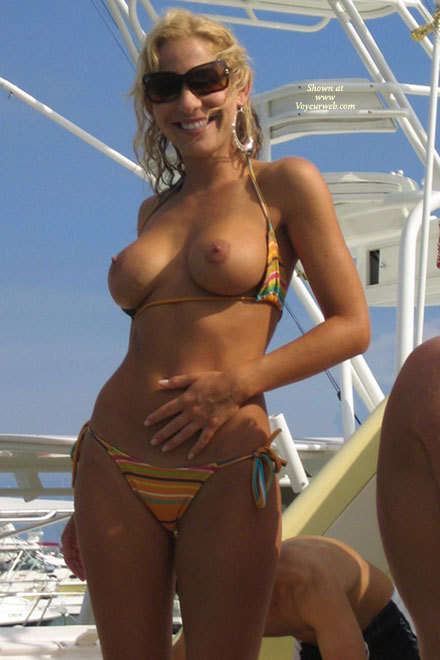 Topless On Boat - Sunglasses, Topless , Tanned Skin, Striped String Bikini, Hoop Earrings, Striped Bikini, Striped Halter Neck Bikini Top, Tie Sided Striped Bikini Pants, Tits Out, Exposed Tits On Boat, Flash Tits, Bikini, Large Round Tits
