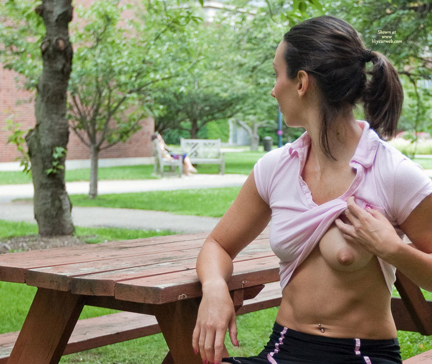 Woman Flashing Her Breast At Picnic Table - Brunette Hair, Flashing Tits, Flashing, Topless , Proving She Is Braless, Picnic Tit, Topless Friend, Pink T-shirt, One Medium Breast, Braless Tit Flash, Picnic Flasher, Pointed Nipple