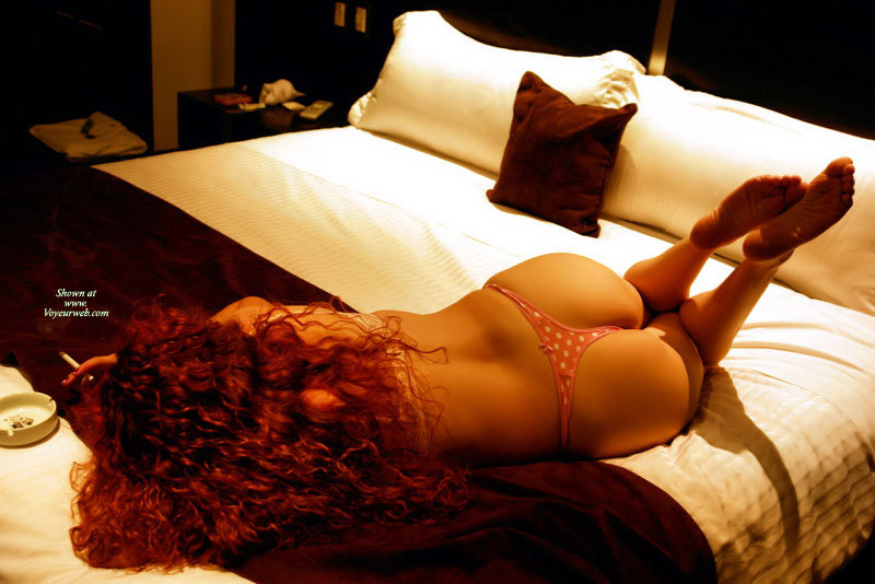 Smoke-in Redhead On Bed - Long Hair, Red Hair , Red Curly Hair, Victorias Secret White Polka Dotted Thong, Bronze Colored Skin, Long Curly Hair, Sole Of Feet, Back View, Cute Ass, Barefeet, Butt Floss