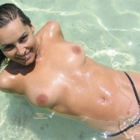 Topless Laying Back In The Surf - Black Hair, Brown Hair, Topless , Black Pussy Thong, Medium Length Brown Hair, Beach Shot, Black G String, Medium Breasts, Nice Smile, Devlish Smile, Topless Laying In Shallow Water, Black Micro Thong, Topless Girl At Beach
