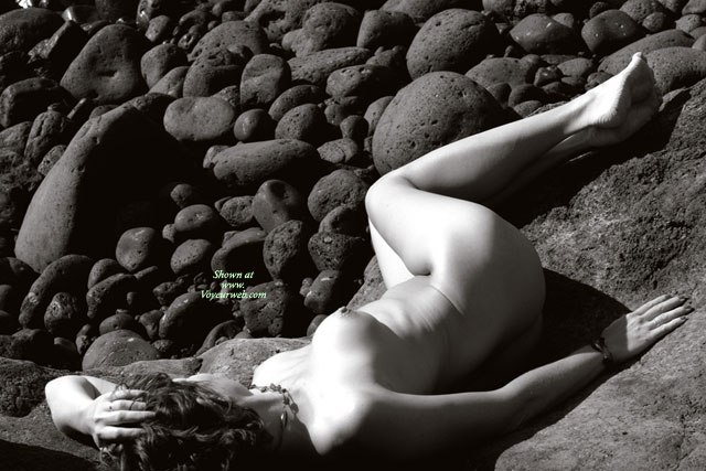 Nude Model Laying Prone On Rocks - Naked Girl, Nude Amateur , Black And White Photo, Puffy Areolas, Artistic Implied Nude, Curvy Feminine Hips, Photo Taken From Above And Slightly Behind The Model, Round And Firm, Artistic On The Rocks, Left Naked On The Rocks, Legs Are Slightly Bent And Turned Away From Camera