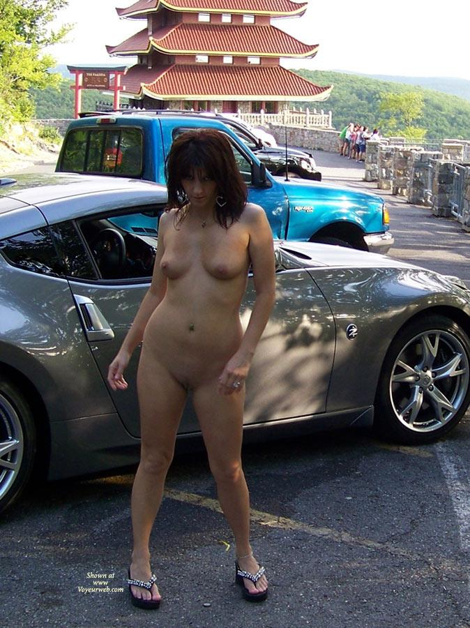 "Posing With The Car Guys - Brunette Hair, Exposed In Public, Nude In Public , We Were Out Taking Pics Around The Local Landmarks Earlier This Summer When We Came Across These Guys Hanging Out On The Side Of The Road With Their Cars.  We Rolled Up And Asked If We Could Take Some Pics Of Monique With Their Rides.  Monique Called Out, ""I'm Naked!"" And Shook Her Tits At Them.  So We Swung Around, Parked, And Monique Jumped Right Out And Started Posing With The Blue Car.  The Dude With The Socks And Sandals Was Taken By Surprise And Almost Flipped Out That Someone Would Actually Touch His Car...until He Realized It Was A Naked Chick.  Then All Was Right In His World."