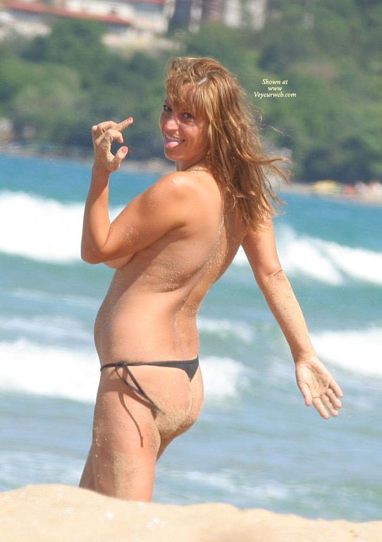 Topless Girl In Thong At The Beach Flipping The Bird And Sticking Her Tongue Out - Brown Hair, Long Hair, Topless, Naked Girl, Nude Amateur , Side View Of Boob, Long Brown Hair At The Beach, Tongue Sticking Out, Nude Beach Girls, Flipping The Bird Topless, Black Thong Bikini Bottoms Only