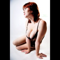 Cleavage - Large Breasts, Milf, Red Hair , Large Handful Of Breasts, Black Vinyl Corsette, Black Corsett, Looking Into Distance, Red Lips, Low Cut Top, Milf Shot Against A White Backdrop, Black Bodysuit