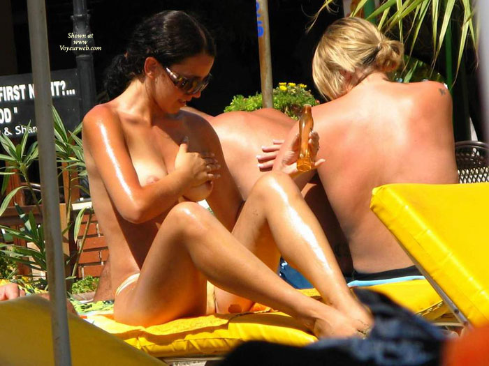 Two Topless Girls Rubbing Suntan Oil Onto Their Bare Breasts. - Topless , Feet Together, Women Applying Suntan Oil On Lounges, Knees Bent, Touching Her Tits, Girl Rubbing Lotion On Her Nips, Tanning Topless, Putting On Tanning Oil, Topless Tanning, Tanning By Pool, Rub On Tan Lotion, Hot Babes Oiling Up