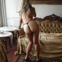Girl In G-string, Standing With Naked Buttocks Facing Photographer - Blonde Hair, Long Hair, Round Ass , G-string, Pear Shaped Ass, Bent Over A Chair, Rear View, Blonde Hair, Rear View Standing By Couch