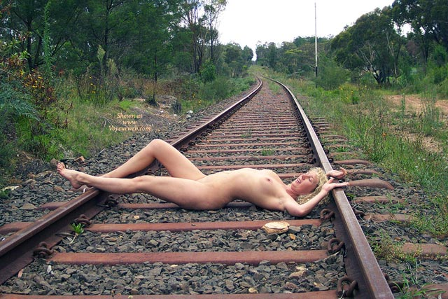 girl sitting on railroad tracks legs open