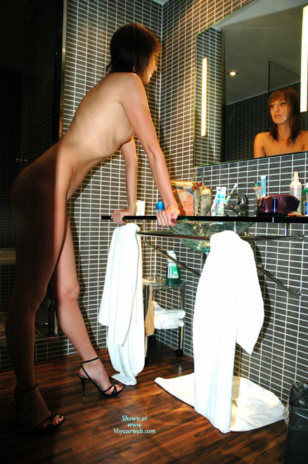 Beauty In A Bathroom - Heels , Looking In Mirror, Leaning On Hands, Leaning On Counter, Black Spike Heels, Admiring Her Reflection In Heels, Red Toenail Polish, Reflection In The Mirror, Bathroom Mirror, Standing Leaning On The Sink