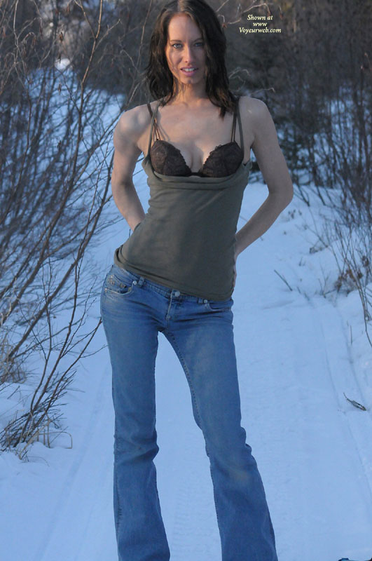 Shirt Pulled Down Exposing Her Bra , Spagetti Strap Khaki Top Pulled Dow Below Bra, Winter And Snow, Looking Straight To Camera, Blue Jeans, Hands On Hips, Brown Embroidered Bra
