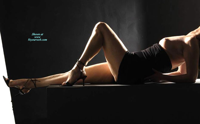 Reclining Full Figure No Face No Pussy , Black Tube Dress, High Heeled Stilettos, Artistic Profile Of Model Laying On Her Back, One Leg Is Stretch Out, The Other Is Bent At Knee