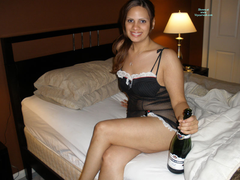 Latina On Bed With Wine - Brunette Hair, Looking At The Camera , Waiting On A Bed, Smiling Into Cam, Drunk Girl Ready To Be Taken Advantage Of, Black Teddy With White Trim, Legs Crossed, Brunette Hair, Negligee And Champagne, Dressed For Sex, Sitting On A Bed