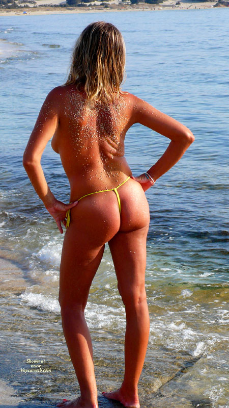 Sand Cookie - Blonde Hair, Topless , Yellow Thong Bikini Bottom, Deep Tan, Sexy Toned Back, Shot From Rear, Topless Blonde, Hands On Hips, Sandy And Sunburnt, Yellow G String, At The Beach, Edge Of Water