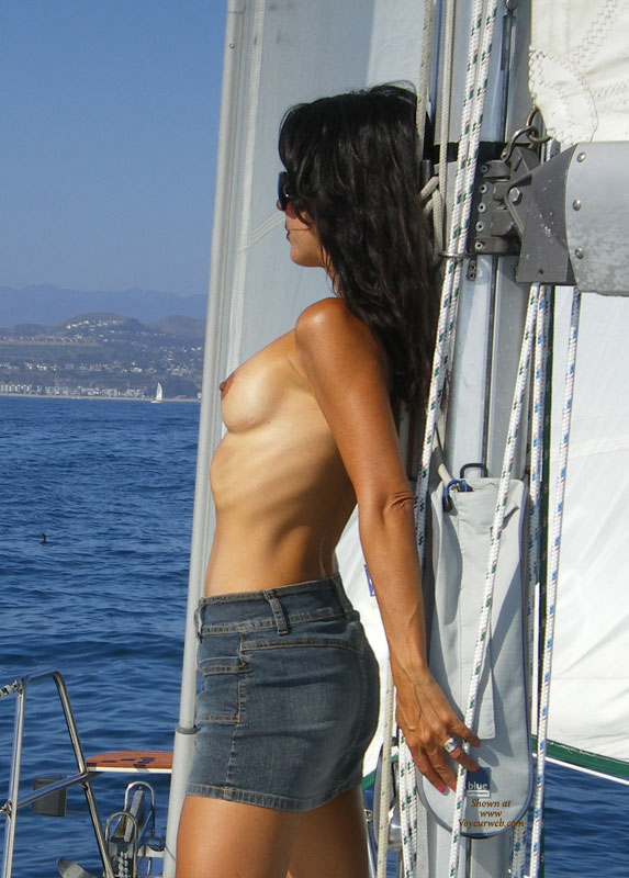 Outdoor Topless Brunette Sailing Leaning On Mast In Mini Skirt - Brunette Hair, Sunglasses, Topless , Small Boobs, Topless Boating, Thin Body, Skinny Body, Topless With Jeans Mini-skirt, Standing With Back To Sailboat Mast, Short Blue Denim Skirt, Topless On A Boat, Posing On A Yacht, Sexy Denim Mini