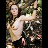 Arms Up And Back Accentuating Her Slim Figure - Topless , Brown Beaded Sarong, Standing In The Woods, Arms Back, Perky Nipples, Beaded Necklace, Topless Amazon, Breasts And Belly Exposed, Topless Forest Pose, Beads And Breasts, Back Arched