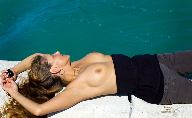 Topless With Long Brown Hair Laying On Seawall By Water - Brown Hair, Hard Nipple, Long Hair, Topless , Laying On A Sea Wall, Medium Sized Boobs With Hard Nipples, Looking Away From Camera, Laying Near Water, Outdoors By Water Topless, Brown Pants With Black Top Pulled Down, Nipples Erect By The Water, Laying On Back, Laying Down Topless With Hands Over Head