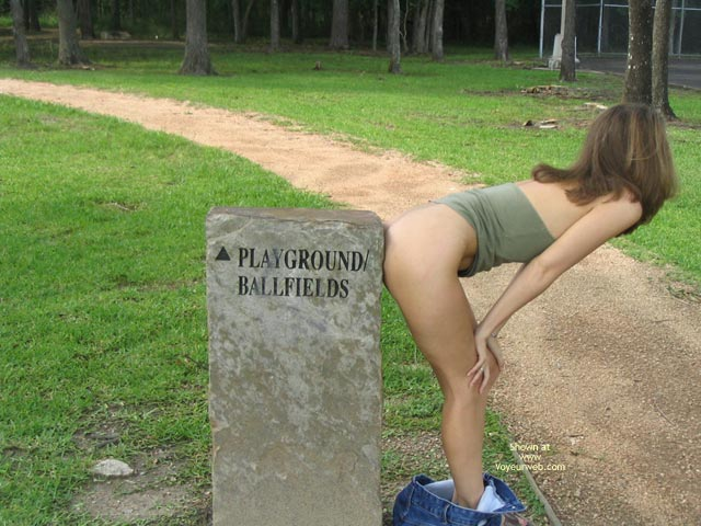 Semi-nude Leaning Over , Semi-nude Leaning Over, Brunette With Dropped Pants, Brunette By Park Path, Jeans Around Ankles To Show Legs And Ass, Sign Pointing To Playground  Ballfields, Blue Jeans, Green Top, Brown Hair