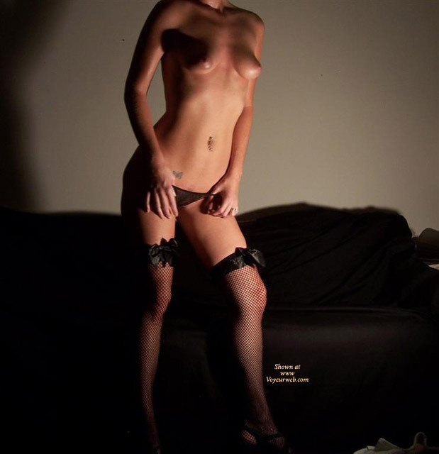 Headless Topless Girl Standing In Front Of A Couch - Navel Piercing, Stockings, Topless , Medium Sized Puffy Areolas, Black Mesh Panties, Black Fish Net Thigh Highs With Bows, Black Mesh Stockings, Belly Tattoo, Fishnet Stockings, Black Panties, Standing On Front Of Couch Topless, Standing In Shadow Topless, Very Pert Torso Shot, Standout Boobs, Topless Pose